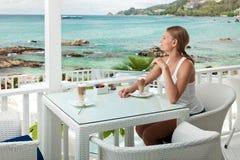 Mädchen, das Kaffeepause in einem Ozeanansichtkaffee hat Stockfotografie