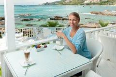 Mädchen, das Kaffeepause in einem Ozeanansichtkaffee hat Lizenzfreie Stockfotografie