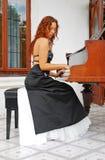 Mädchen, das am Klavier sitzt Lizenzfreie Stockfotos