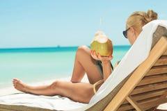 Mädchen, das Kokosnuss hält und auf dem Strand beim sich hinlegen liest Lizenzfreie Stockbilder