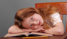 Mädchen, das Kopf auf Schreibtisch niederlegt Stockbilder