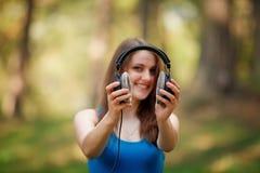 Mädchen, das Kopfhörer hält stockbild