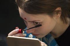 Mädchen, das Kosmetik aufträgt Lizenzfreies Stockfoto