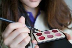 Mädchen, das Kosmetik verwendet Stockbilder