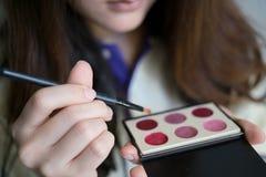 Mädchen, das Kosmetik verwendet Lizenzfreie Stockfotografie