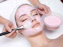 Mädchen, das kosmetische rosafarbene Gesichtsschablone empfängt Stockbilder