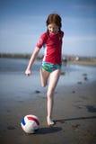 Mädchen, das Kugel auf Strand tritt Stockbild