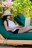 Mädchen, das Laptop beim Haben ihres Feiertags verwendet Stockfotos