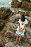 Mädchen, das Laptop draußen auf Felsen verwendet Lizenzfreie Stockfotografie