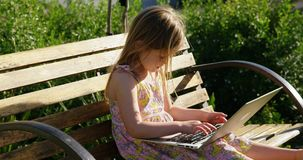 Mädchen, das Laptop im Garten 4k verwendet stock video footage