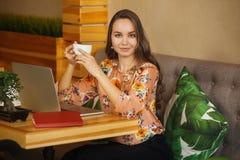Mädchen, das am Laptop sitzt und eine Schale hält stockbild