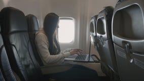 Mädchen, das Laptop verwendet, während im flachen nahen Fenster sitzt stock video