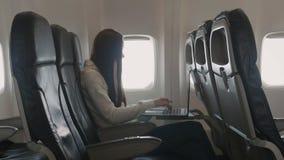 Mädchen, das Laptop verwendet, während im flachen nahen Fenster sitzt stock video footage