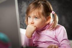 Mädchen, das Laptopbildschirm betrachtet Stockbilder