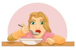 Mädchen, das Lebensmittel am Tisch isst Stockbilder