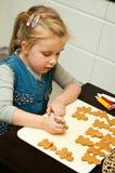 Mädchen, das Lebkuchenplätzchen für Weihnachten macht Stockfotografie