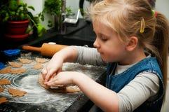 Mädchen, das Lebkuchenplätzchen für Weihnachten macht Lizenzfreies Stockbild