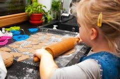 Mädchen, das Lebkuchenplätzchen für Weihnachten macht Lizenzfreie Stockbilder