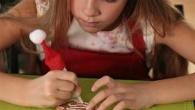 Mädchen, das Lebkuchenweihnachtsplätzchen verziert stock video footage