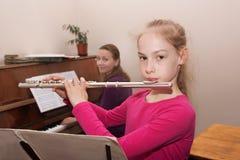 Mädchen, das lernt, die Flöte zu spielen Stockfotografie