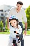 Mädchen, das lernt, ein Fahrrad mit ihrem Vater zu reiten Lizenzfreies Stockbild