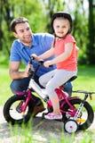 Mädchen, das lernt, ein Fahrrad mit ihrem Vater zu reiten Stockbild