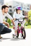 Mädchen, das lernt, ein Fahrrad mit ihrem Vater zu reiten Stockfotos