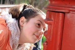 Mädchen, das Loch des roten britischen Postbox betrachtet Lizenzfreies Stockfoto