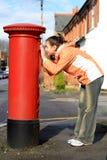 Mädchen, das Loch des roten britischen Postbox betrachtet stockfotos