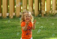 Mädchen, das Luftblasen jagt Stockbilder