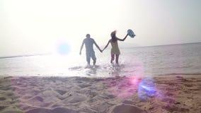 Mädchen, das männliche Hand und Betrieb auf tropischem exotischem Strand zum Ozean hält Follow-meschuß der jungen Frau ziehen sie stock video footage
