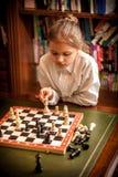 Mädchen, das Maßnahme auf Schachbrett trifft Lizenzfreie Stockfotos