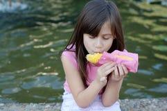 Mädchen, das Mais isst stockfoto
