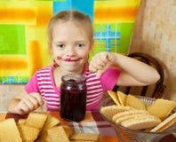 Mädchen, das Marmelade vom Glas isst Stockfotos