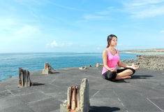Mädchen, das Meditation auf dem Strand tut Stockfotografie