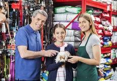 Mädchen, das Meerschweinchen mit Vater-And Saleswoman In-Speicher hält lizenzfreie stockfotografie