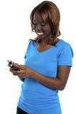 Mädchen, das Meldung durch ihr Mobiltelefon sendet Stockfoto