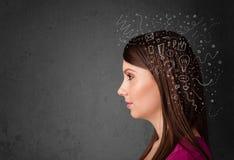 Mädchen, das mit abstrakten Ikonen auf ihrem Kopf denkt Stockfotografie