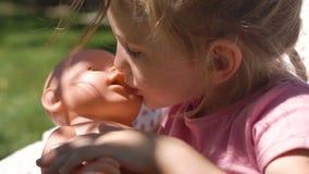Mädchen, das mit Baby - Puppe im Hinterhof spielt stock footage
