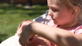 Mädchen, das mit Baby - Puppe im Hinterhof spielt stock video