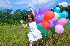 Mädchen, das mit Ballonen läuft Lizenzfreie Stockfotografie