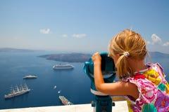Mädchen, das mit Binokeln in Santorini Griechenland schaut Stockbilder