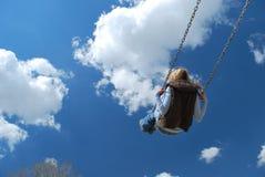 Mädchen, das mit blauem Himmel schwingt Lizenzfreie Stockbilder