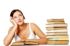 Mädchen, das mit Buch und dem Denken sitzt. lizenzfreies stockbild