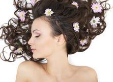 Mädchen, das mit bunten Blumen in ihrem Haar liegt Lizenzfreie Stockbilder