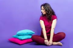 Mädchen, das mit bunten Kissen auf einem purpurroten Hintergrund sitzt Stockbild