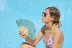 Mädchen, das mit dem Ventilator durch das Pool abkühlt Stockfotos