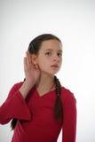 Mädchen, das mit der Hand auf Ohr hört stockbild
