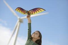 Mädchen, das mit Drachen am Windpark spielt Stockfotografie