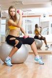 Mädchen, das mit Dumbbell in der Eignunggymnastik auf Kugel aufwirft Stockfotos